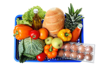 Shopping basket with grocery products on white background, top view
