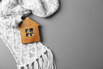 Wooden house model and scarf on grey background, top view with space for text. Heating efficiency Wall mural