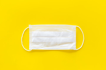 Flu prevention concept. Medical face mask on yellow background top view copy space