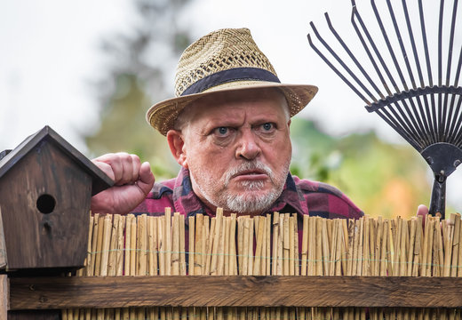 An elderly man in a hat looks angry and watches the neighborhood over a garden fence. Concept: Problems with the neighborhood.