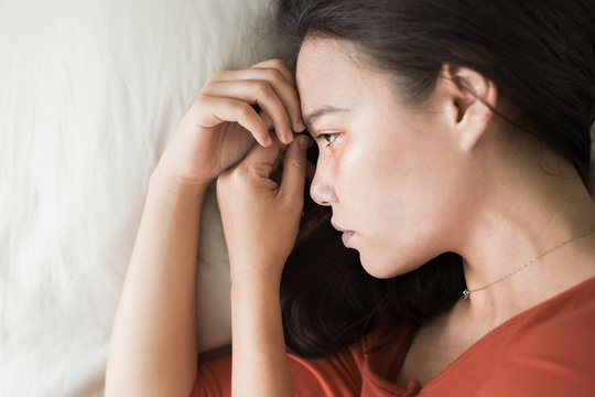A sad depressed woman lying in bed.