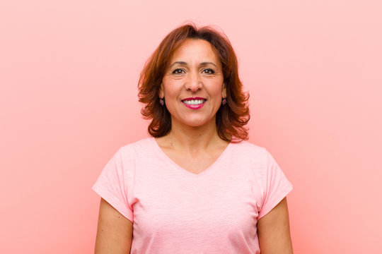 middle age woman smiling positively and confidently, looking satisfied, friendly and happy against pink wall