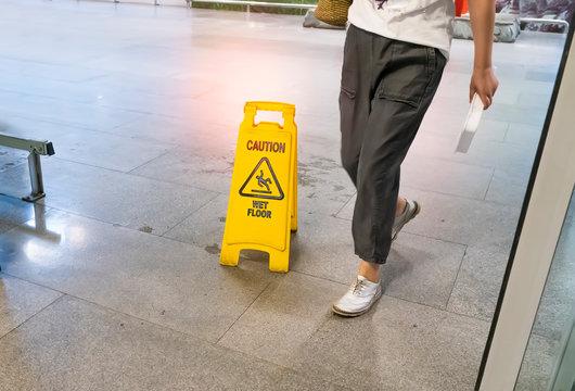 Yellow Caution wet floor sign on wet floor