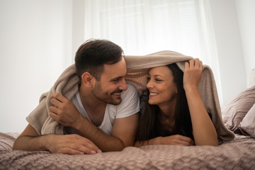 Happy couple is having fun in bed.