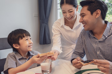 Asian family, father, mother and son having breakfast, bread with jam together in dining room, happy family concept