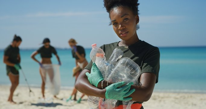 Portrait of an young african female volunteer is smiling in camera satisfied with picking up a plastic litter on a beach with a sea to protect an environment.