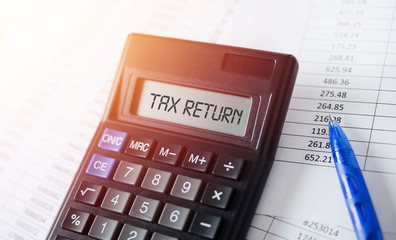 Word Tax Return on calculator. Business and tax concept.