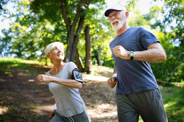 Mature or senior couple doing sport outdoors, jogging in a park