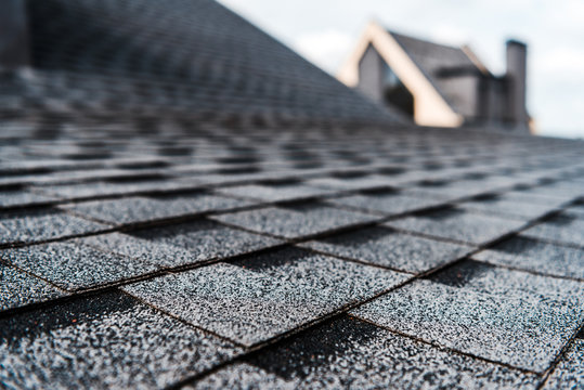 selective focus of grey shingles on rooftop of building