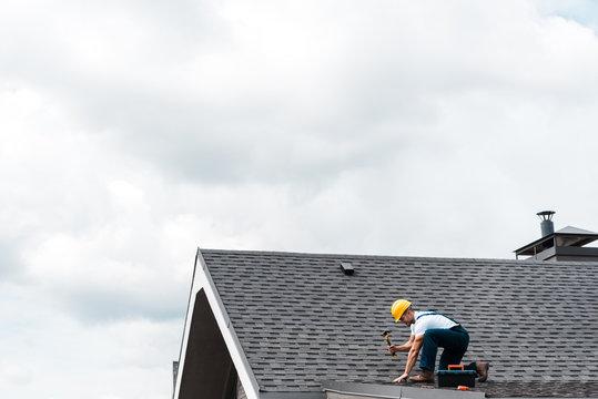 repairman in helmet holding hammer while repairing roof