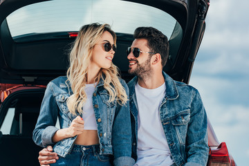 Fotomurales - attractive woman and handsome man in denim jackets smiling outside