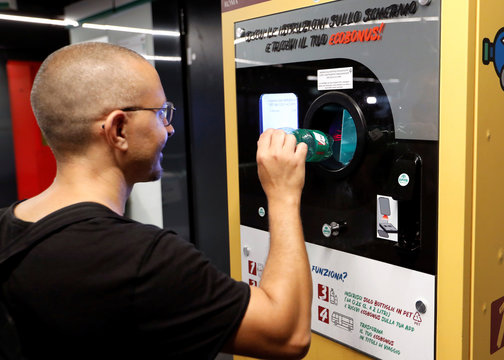 A man puts a plastic bottle into a recycling machine in San Giovanni metro station in Rome