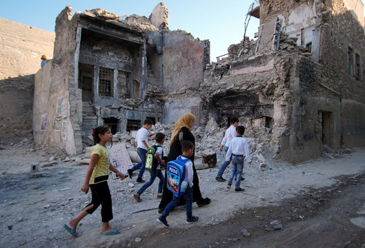 A woman walks with her kids on the first day of the new school term in the old city of Mosul
