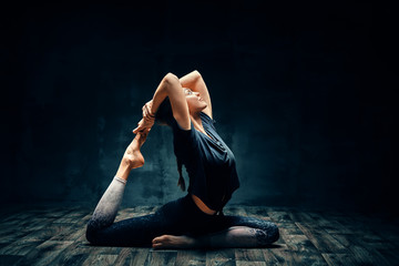 In de dag School de yoga Young woman practicing yoga doing one legged king pigeon pose in dark room