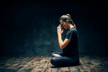 Rear view of young woman practicing yoga sitting in lotus pose with namaste in dark room and copy space