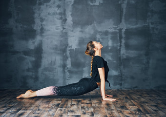Young woman practicing yoga, doing cobra Pose on dark background