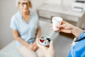 Nurse carrying water and pill box with medicine for a senior woman, taking care of an elder patient...