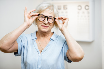 Portrait of a happy senior woman wearing eyeglasses in front of eye chart in ophthalmology office. Concept of checking eyesight and selecting glasses in older age