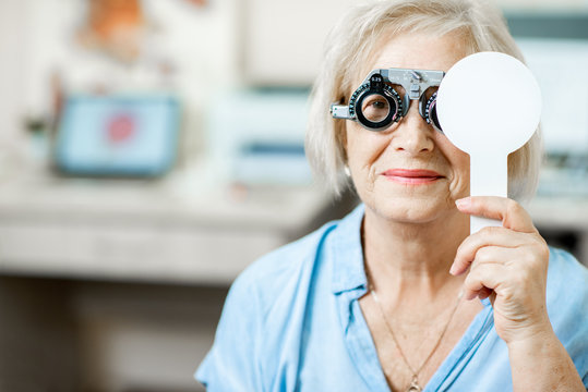 Senior woman checking vision with eye test glasses and scapula during a medical examination at the ophthalmological office
