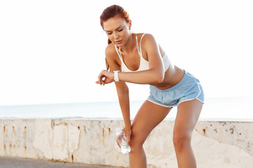 Image of slim young woman holding water bottle and looking at wristwatch while doing workout by seaside in morning Fototapete