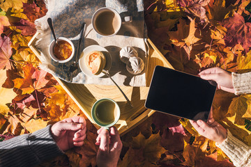 Couple of young people are taking a picture on a tablet of morning breakfast on a wooden tray in the autumn park with colorful maple leaves. Aerial view
