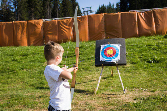 Little boy using bow and arrow and aiming at the target.
