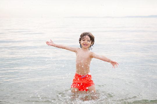Smiling boy splashing water at beach