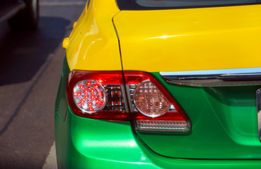 Close up modern detail red light  car and vintage. Yellow and green Taxi Thailand.