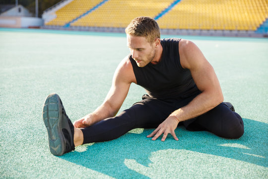 Image of healthy man stretching his body at sports ground outdoors