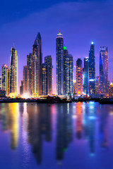Dubai marina skyline at night with water reflections, United Arab Emirates