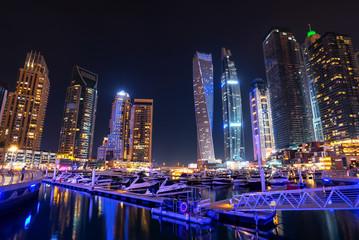 Wall Mural - Dubai marina skyline at night with boats in the harbor, United Arab Emirates