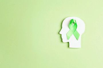 World mental health day concept. Green awareness ribbon with brain symbol on a green background. Wall mural