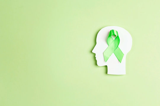 World mental health day concept. Green awareness ribbon with brain symbol on a green background.