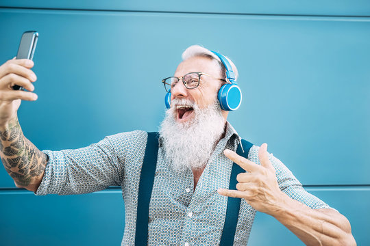 Senior crazy man taking self video while listening music with headphones - Hipster guy having fun using mobile smartphone playlist apps - Happiness, technology and elderly lifestyle people concept