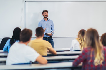 Young students listening to professor in the classroom on college
