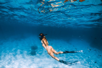 Freediver girl with fins glides over sandy bottom in ocean Wall mural
