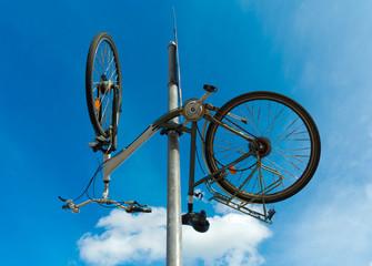 altes Fahrrad hängt verkehrt herum am Verkehrsschild