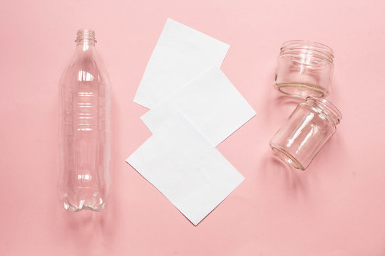 municipal solid waste. plastic bottles, paper and two glass jars on a pink background
