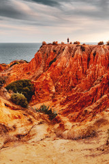 Rough washed out sand stone rocks at the coast at colorful and dramatic sunset light. Praia da Marinha, Famous Beach, Algarve Coast in South Portugal, Atlantic Ocean