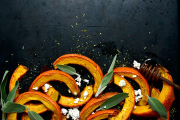 Baked pumpkin slices with honey, sage and ricotta. Top view with copy space.