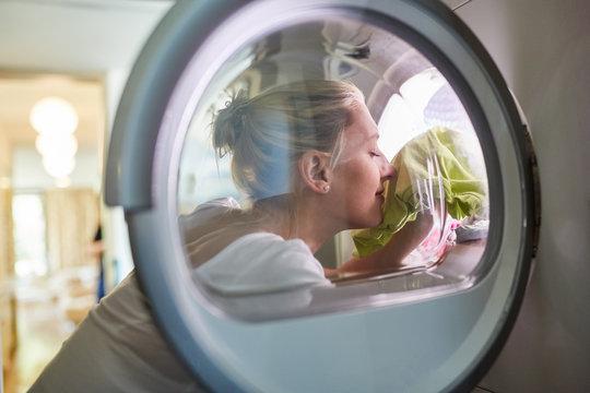 Hausfrau mit frischer Wäsche in der Waschmaschine