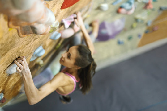 Young Woman Rock climber is Climbing At Inside climbing Gym. slim pretty Woman Exercising At Indoor Climbing Gym Wall