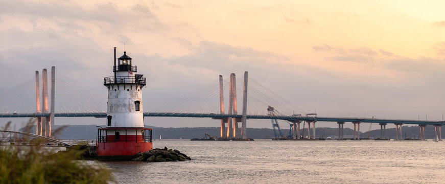 Panorama of a caisson (sparkplug) style lighthouse under soft golden light with a bridge in the background. Tarrytown Light on the Hudson River in New York.