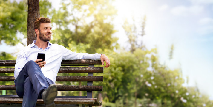 young handsome business man in suit relax on bench in park