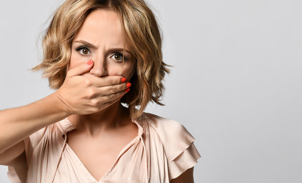 shocked woman covers her mouth, looks shy, expressing silence and misconceptions, frightened