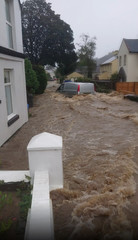 A car is seen in a flooded street in Laxey