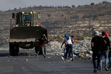 Demonstrator hurls a bottle at an Israeli military machinery during a protest to show solidarity with Palestinian prisoners held in Israeli jails, near the Jewish settlement of Beit El in the Israeli-occupied West Bank