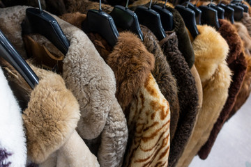 Rail of Secondhand Fur Coats For Sale in a Thrift Store Shop