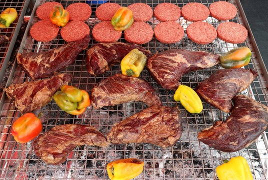 Grilled angus ribs along with yellow peppers and beef burger on a large barbecue.