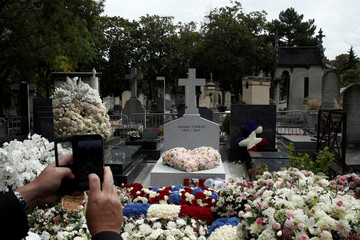Man takes a picture of the tomb of late French President Jacques Chirac after his burial at the Montparnasse cemetery in Paris